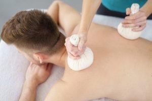 Mann genießt eine Kräuterstempel-Massage bei der Heilpraxis Valeovia in Bremen