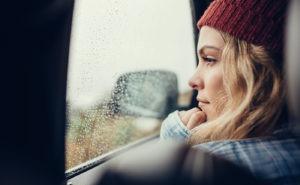 Frau schaut traurig aus dem Autofenster
